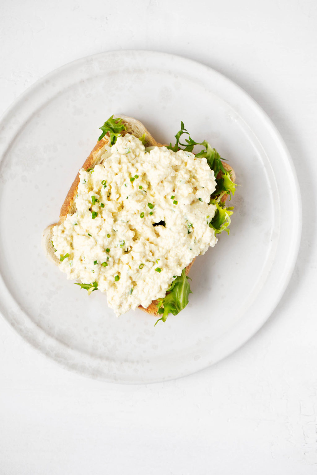 A slice of toast has been covered in a vegan tofu egg salad and a single green slice of lettuce. It rests on a white ceramic plate.