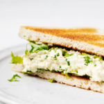 A toasted sandwich has been prepared with a vegan tofu egg salad. It's plated on a white ceramic plate.