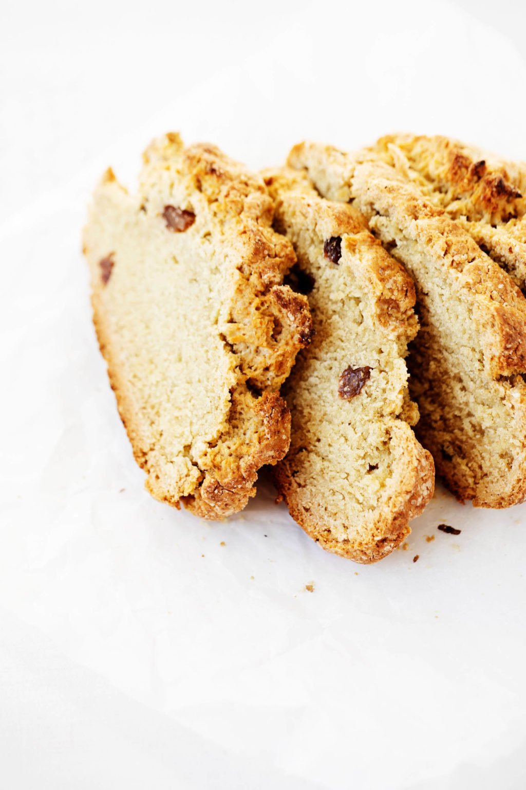 A few slices of vegan Irish soda bread, lined up on a white sheet of parchment paper.