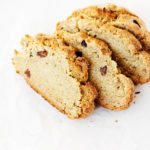 Four rustic slices of a dense, vegan Irish soda bread are placed on a white surface.