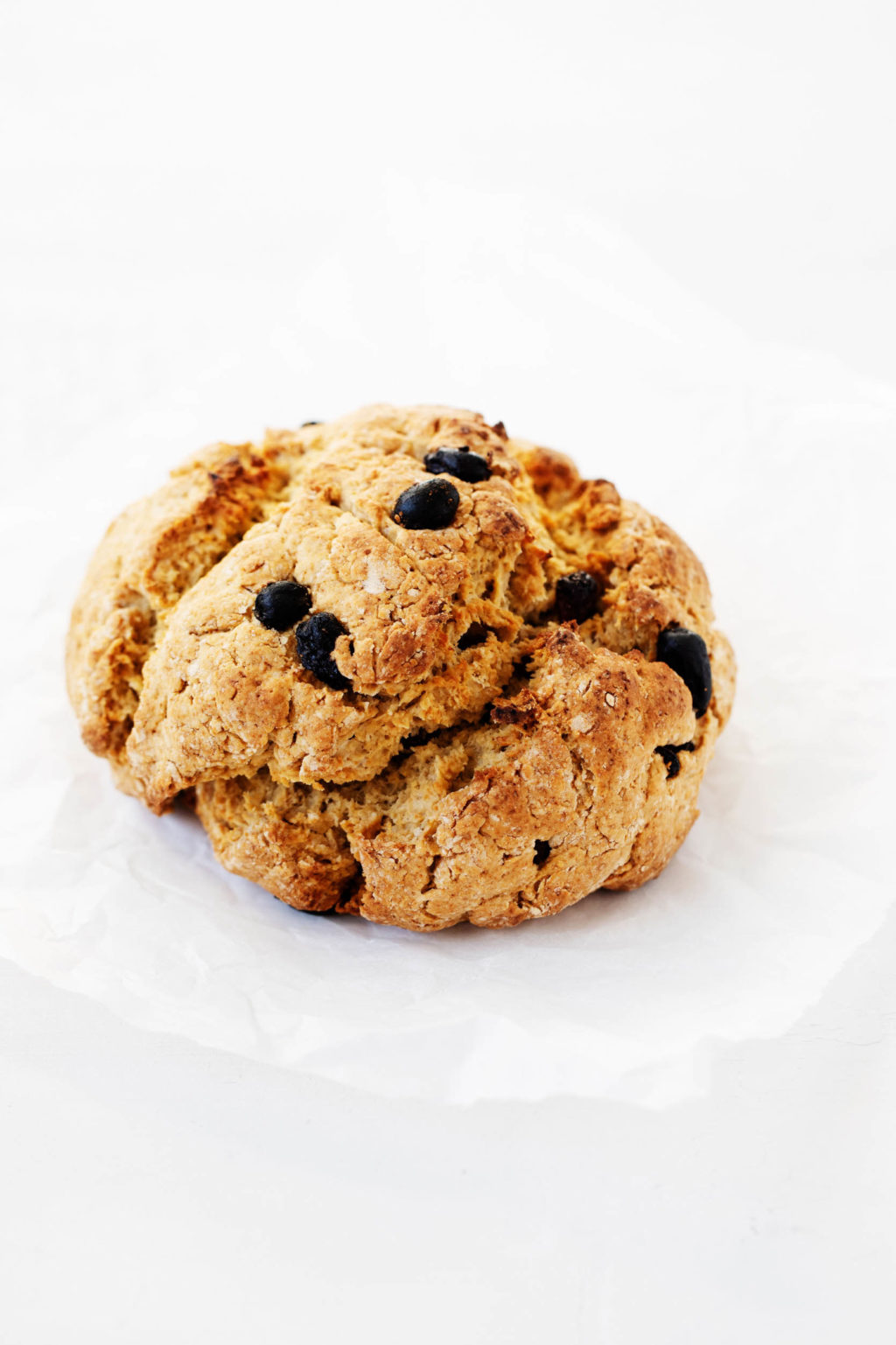 A round, rustic quick bread has been studded with currants and laid out on a sheet of white parchment paper.