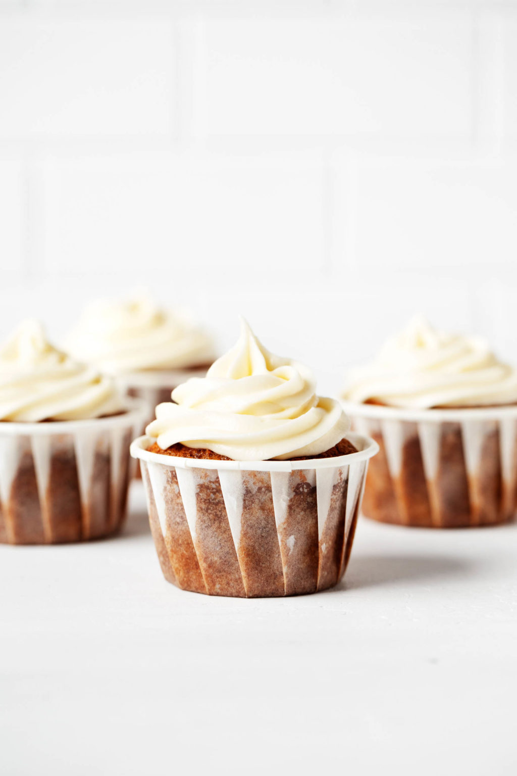 Los cupcakes de pastel de zanahoria vegano helado están alineados uno al lado del otro contra un fondo brillante.