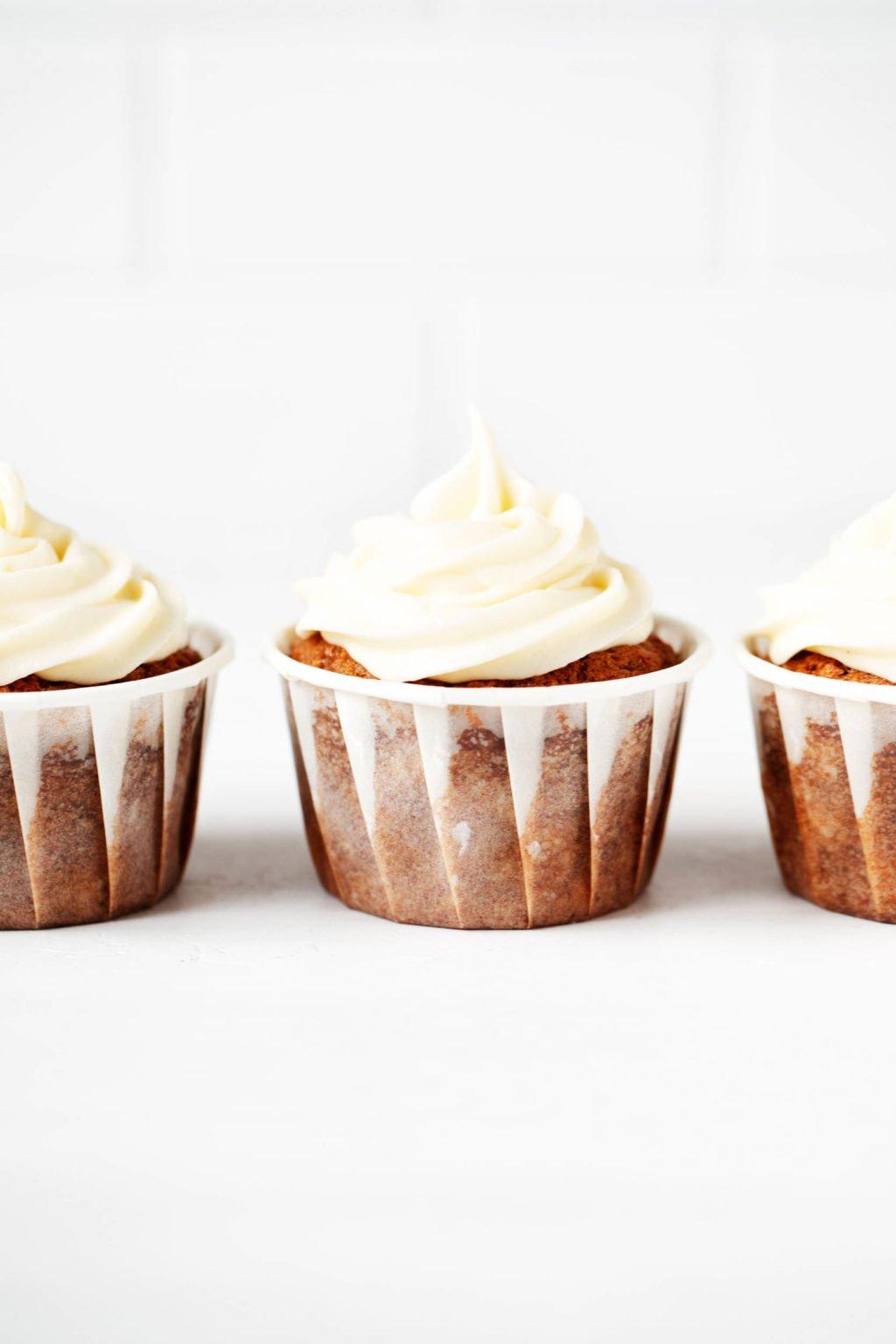 Tres cupcakes veganos, hechos con zanahorias y glaseado de queso crema, están alineados cuidadosamente frente a una superficie de ladrillo blanco.