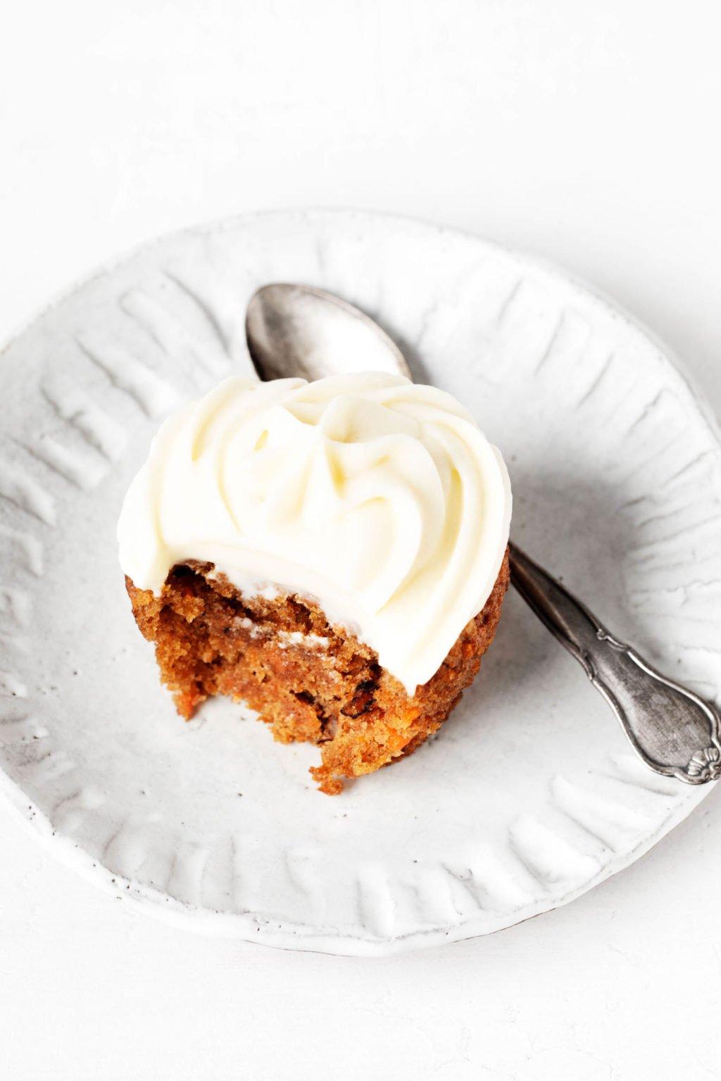 Un solo cupcake de pastel de zanahoria vegano descansa sobre un pequeño plato blanco de cerámica.  Hay una cuchara pequeña al lado de la magdalena.