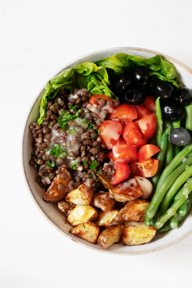 A round, white salad bowl has been filled with the colorful ingredients for a vegan Niçoise salad, including tomatoes, lentils, potatoes, and green beans.
