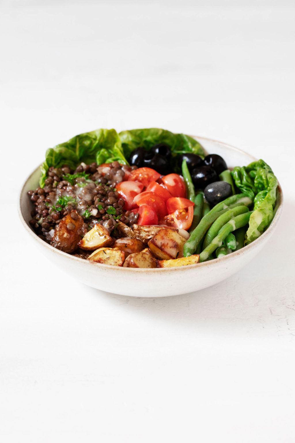 An angled photo of a round bowl of vegetarian lentil Niçoise salad, which is placed on a clean white surface.