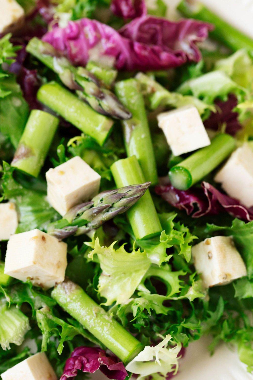 Una fotografía cenital ampliada de una ensalada de primavera que ha sido apilada con queso feta de tofu con hierbas.