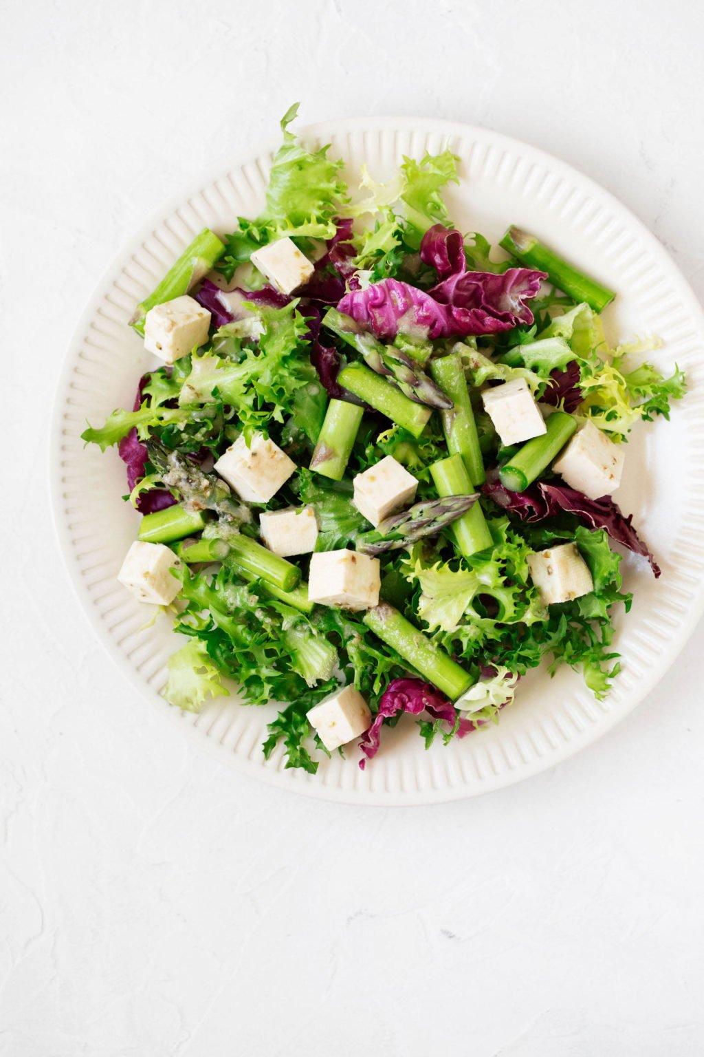 Se sirve una ensalada de primavera brillante y vibrante en un plato de cerámica blanca estriada.  Una mezcla de tofu marinado es parte de la ensalada.