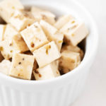 A round, white ramekin has been filled with small cubes of a vegan herbed tofu feta cheese.