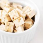 Un ramekin blanco y redondo se ha llenado con pequeños cubos de queso feta de tofu vegano con hierbas.