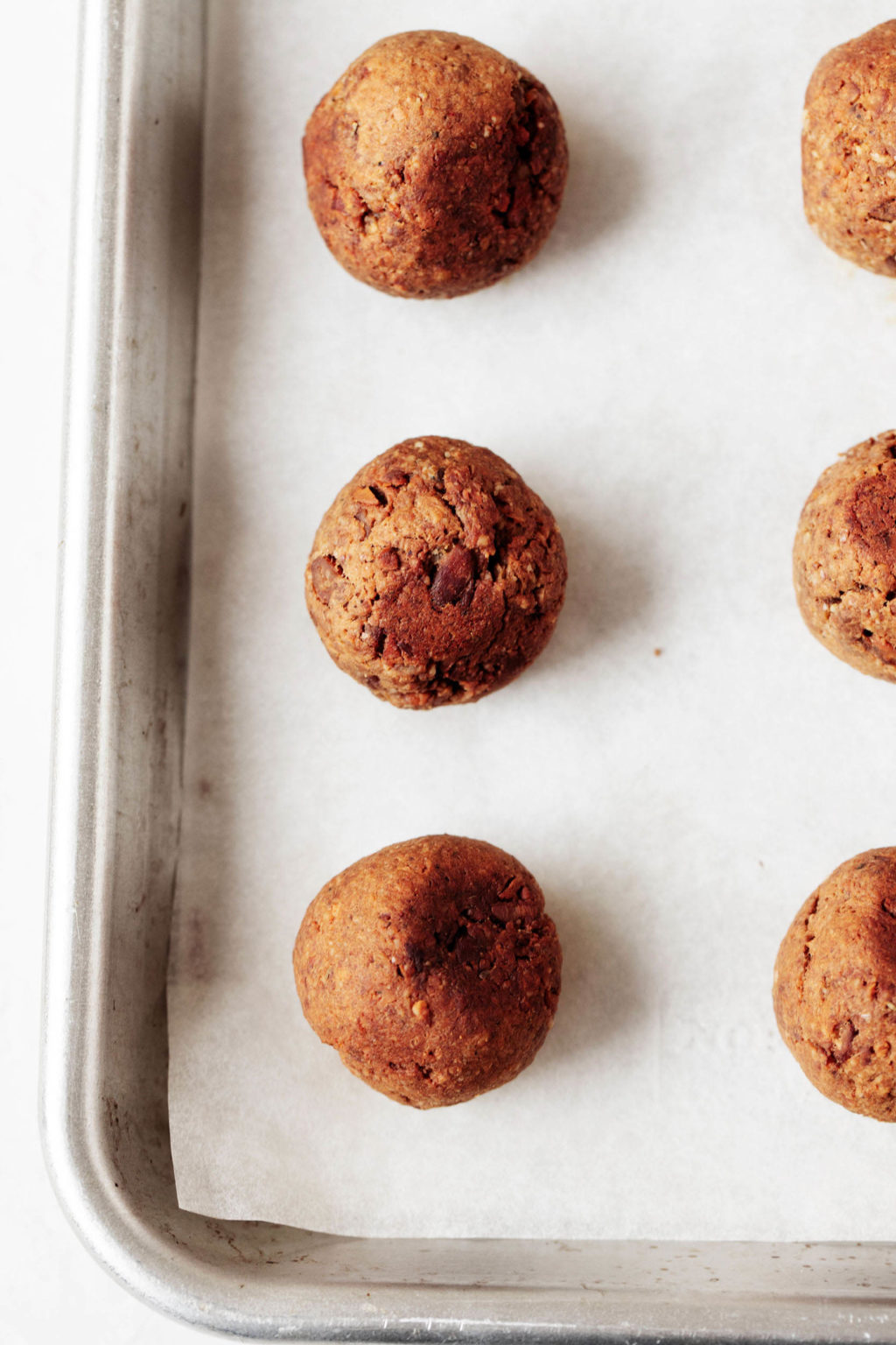 A silver rimmed baking sheet is covered with a sheet of parchment and freshly baked tempeh meatballs.