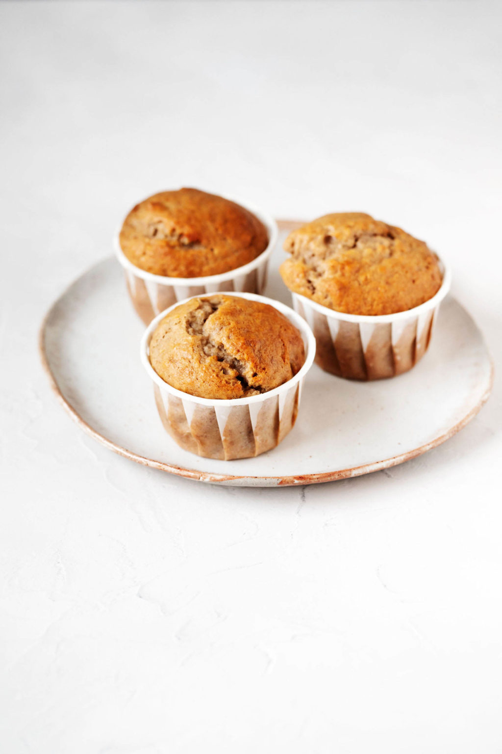 A small, white ceramic plate with a tan rim holds three freshly baked muffins in their muffin liners.