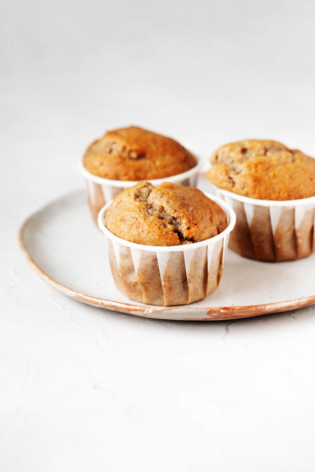 Three vegan banana walnut muffins are arranged on a white ceramic plate. The plate rests on a white surface.