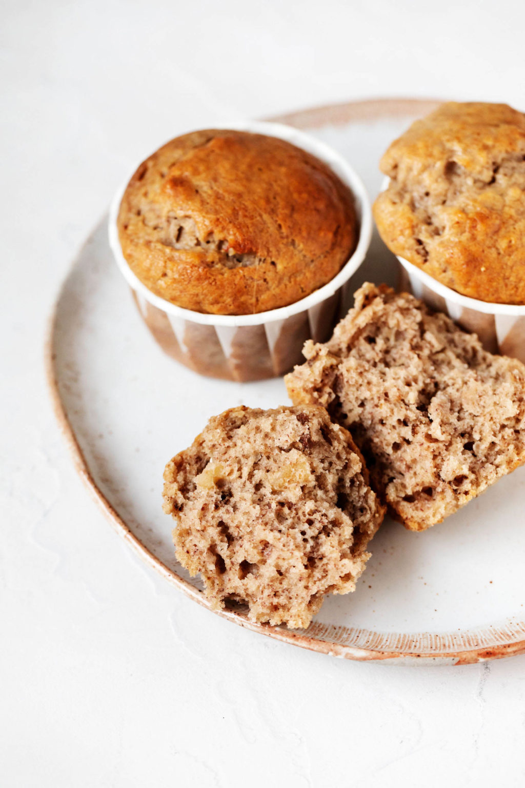 A small dessert plate holds vegan banana walnut muffins. Two are intact, in their liners, while a third has been broken in half.