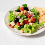 A white fluted plate holds a vegan Greek salad with chickpeas and pita wedges. It rests on a white surface.