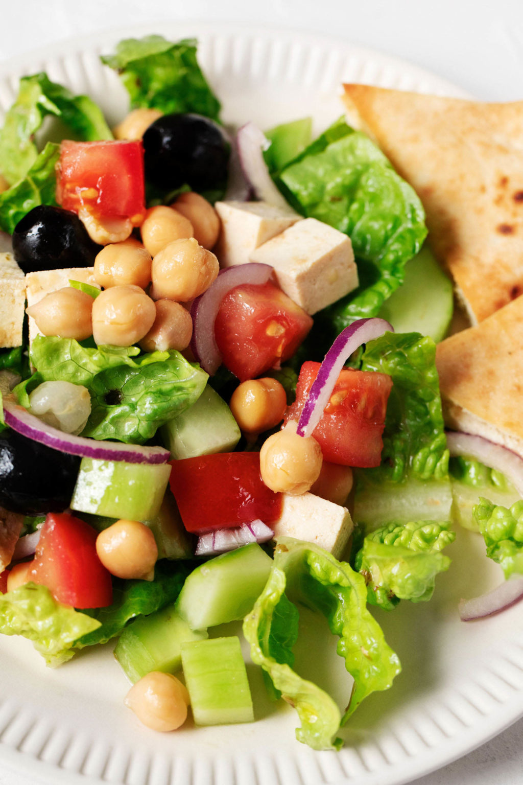 A zoomed in, overhead image of a fresh, summery salad with romaine, tofu, chickpeas, and tomatoes.