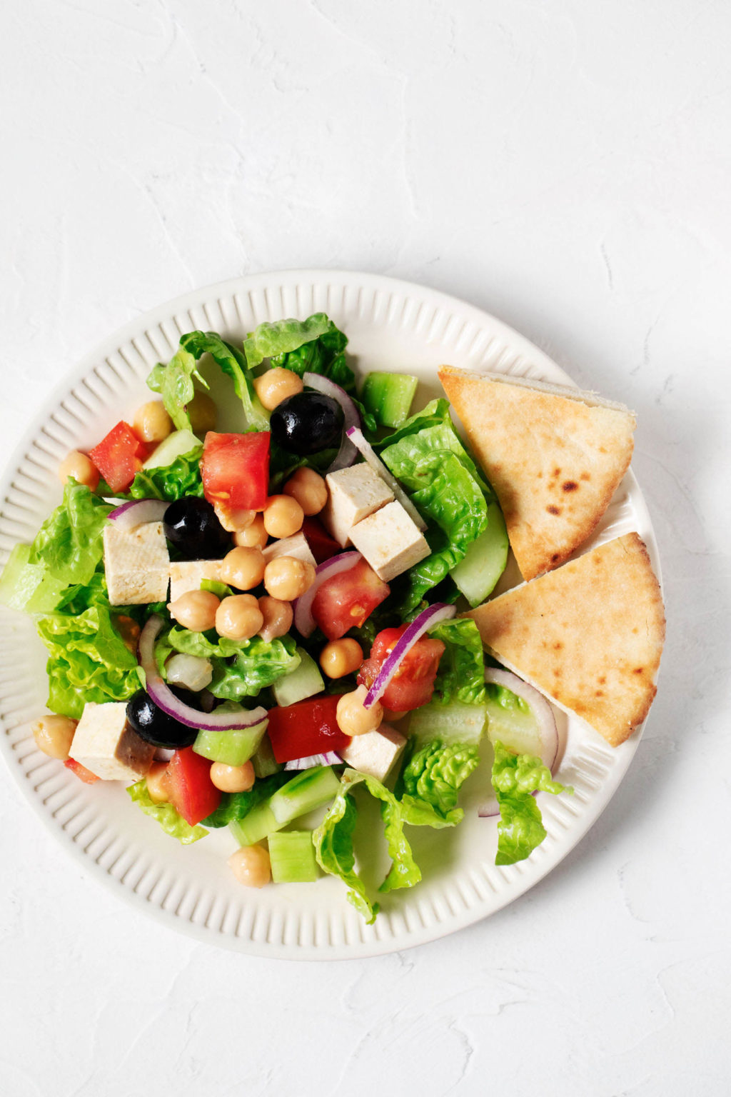An overhead image of a crisp green salad with romaine lettuce, tomatoes, olives, red onions, and pita wedges. It's served on a white, rimmed plate.