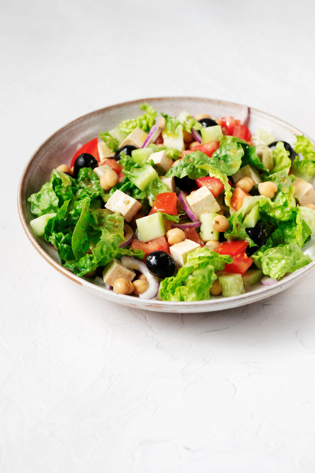 A vegan Greek salad, prepared with tofu feta and olives, is served in a large, round bowl. Crisp green romaine lettuce is folded into the salad.
