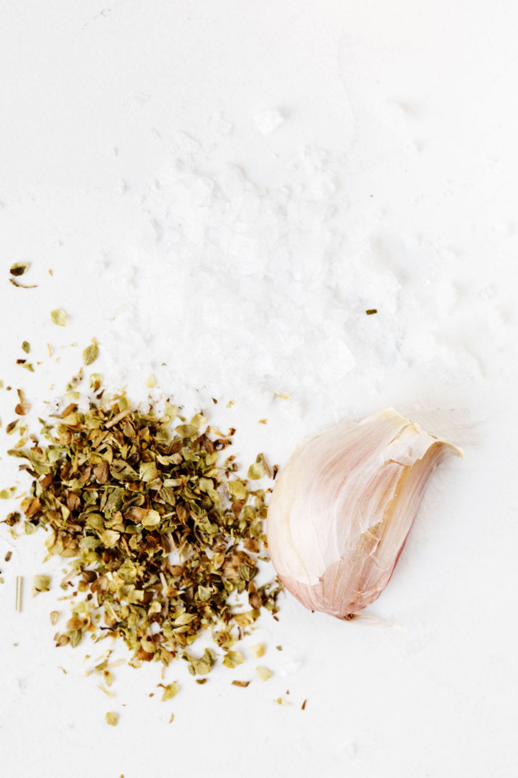 Dried oregano and an unpeeled clove of garlic rest on a white surface.