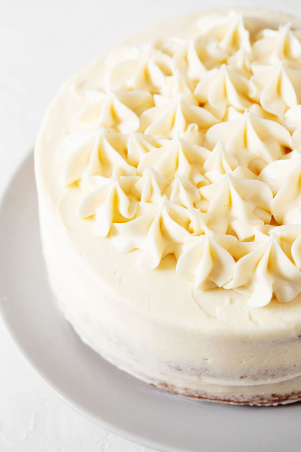 An angled photograph of a white, decorated cake that is resting on a round plate. It's covered in piped buttercream stars.