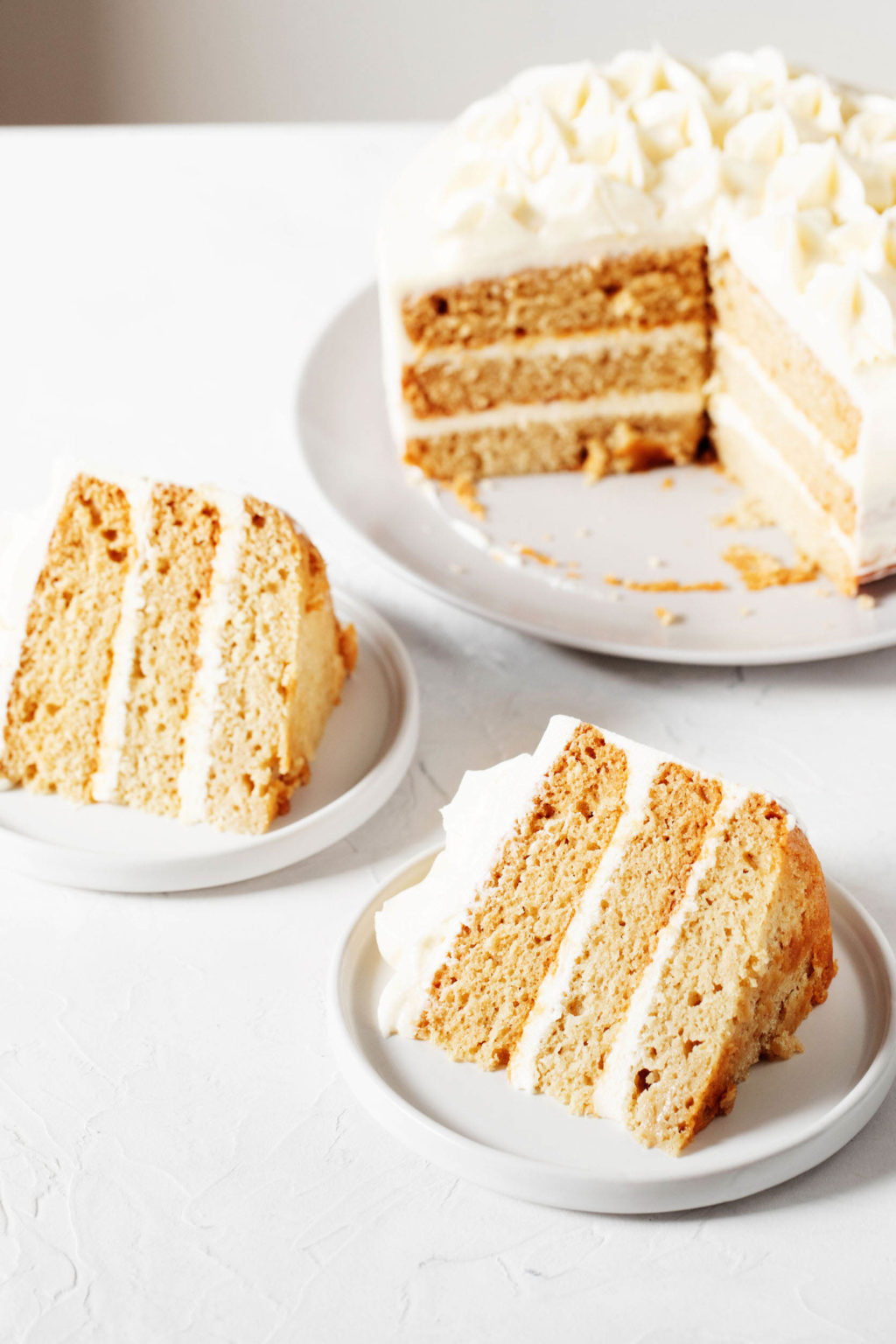 A pale yellow layer cake with whipped, white buttercream frosting has had slices cut out. Two slices rest on small dessert plates on top of the cake, all on top of a white surface.