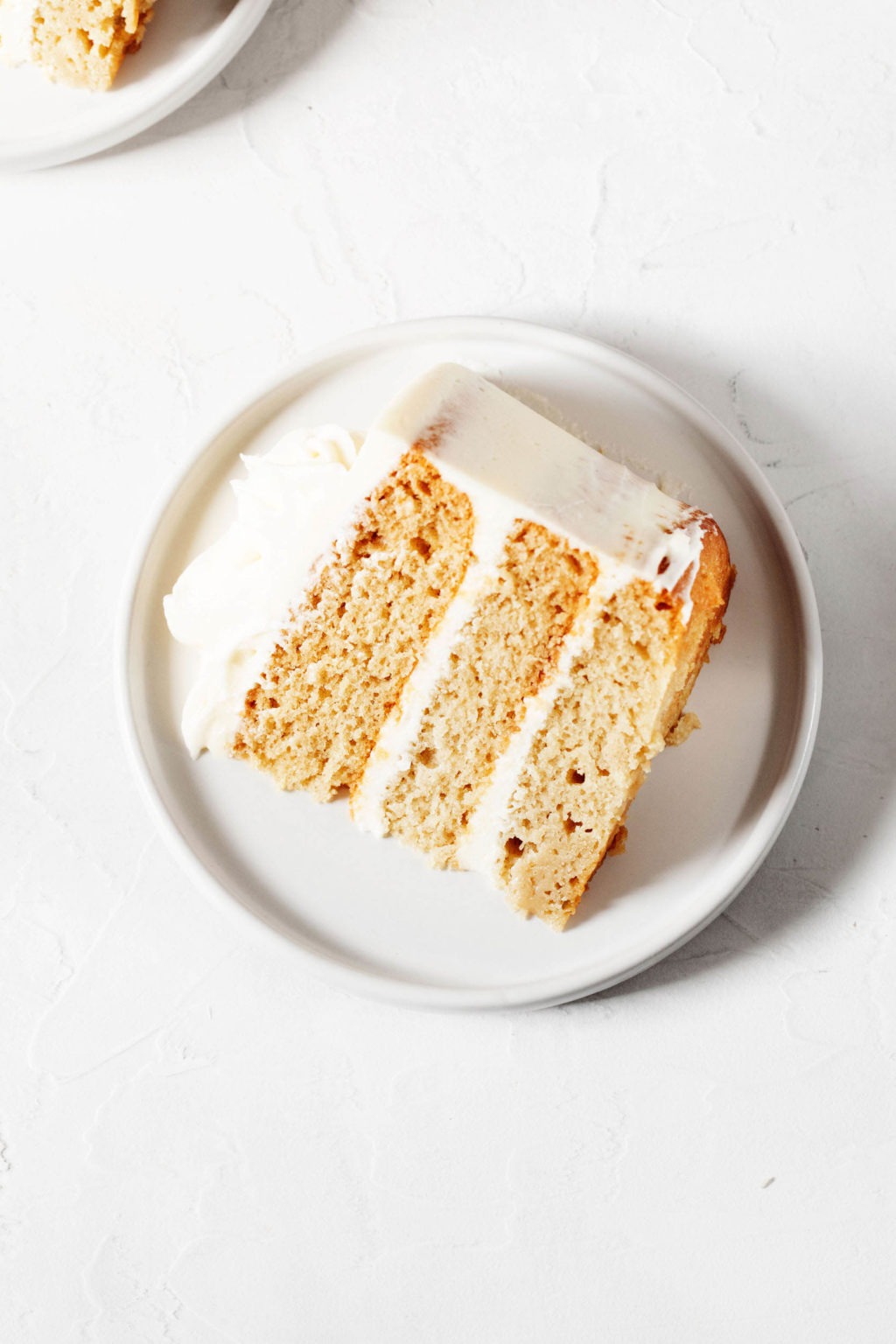 An overhead image of a slice of vegan vanilla cake, which has been sliced and placed onto a round dessert plate.