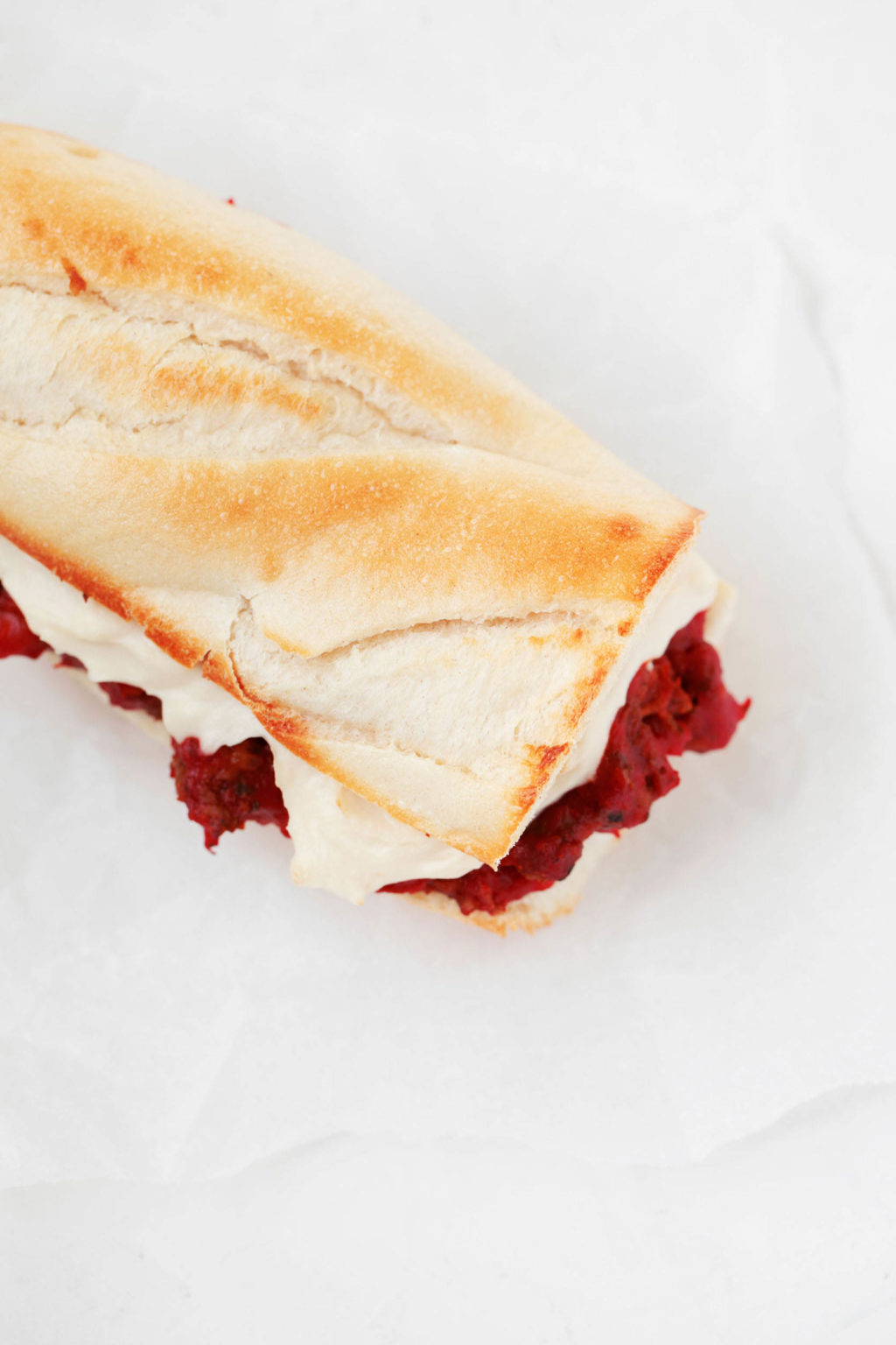 An overhead image of sliced Italian bread, which has been piled with red sauce and a creamy cheese sauce. It rests on a piece of parchment paper.