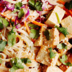 A zoomed in, overhead photograph of a tangle of pad thai noodles, tofu, vegetables, and herbs.