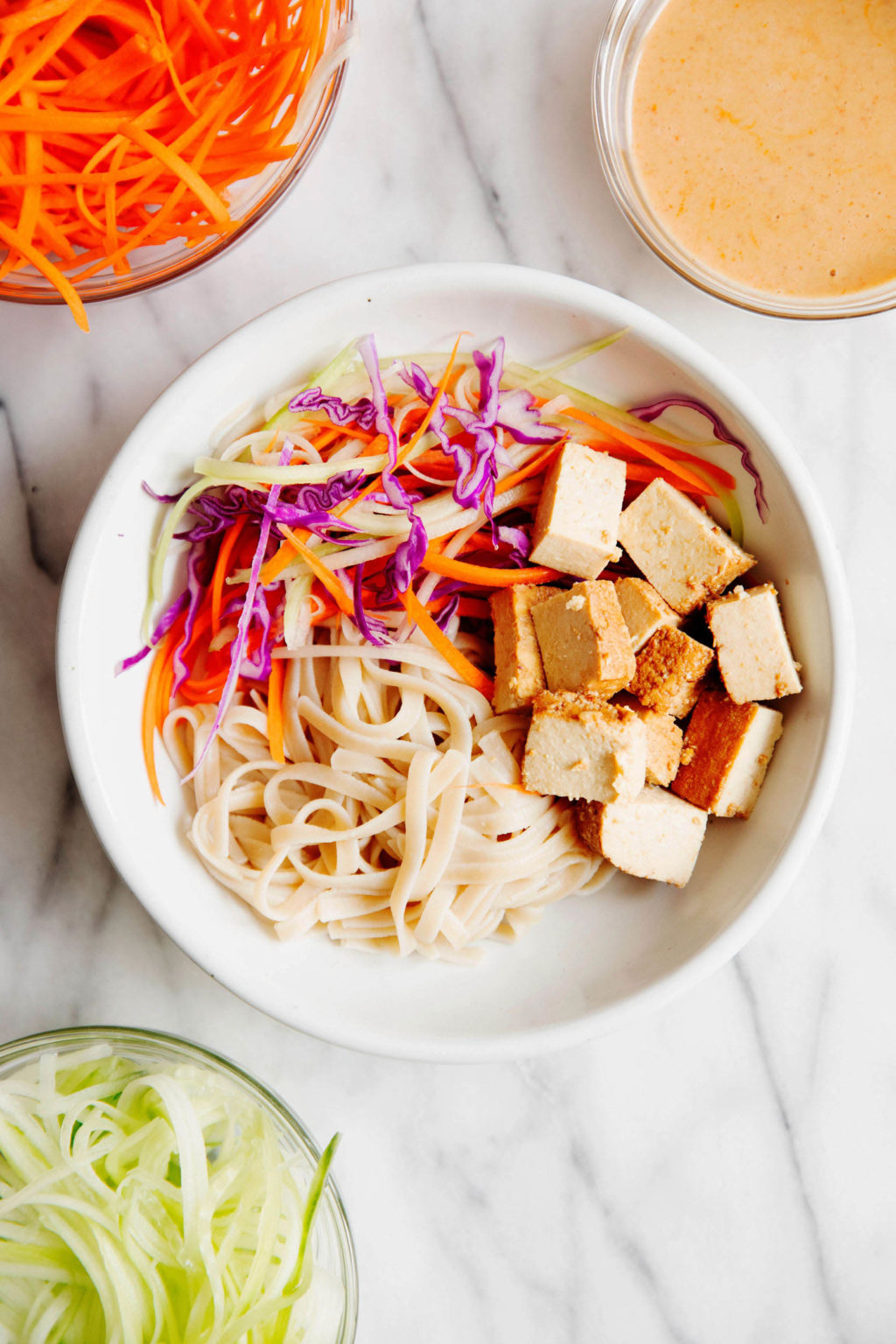 A bowl of tofu, noodles, and vegetables, surrounded by small glass bowls with prepared ingredients in them. The bowls rest on white marble.