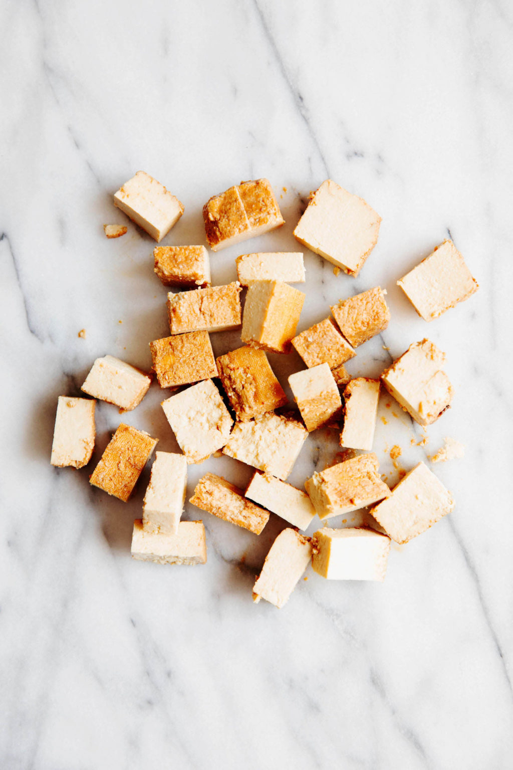 Cubed tofu rests on a white marble surface.