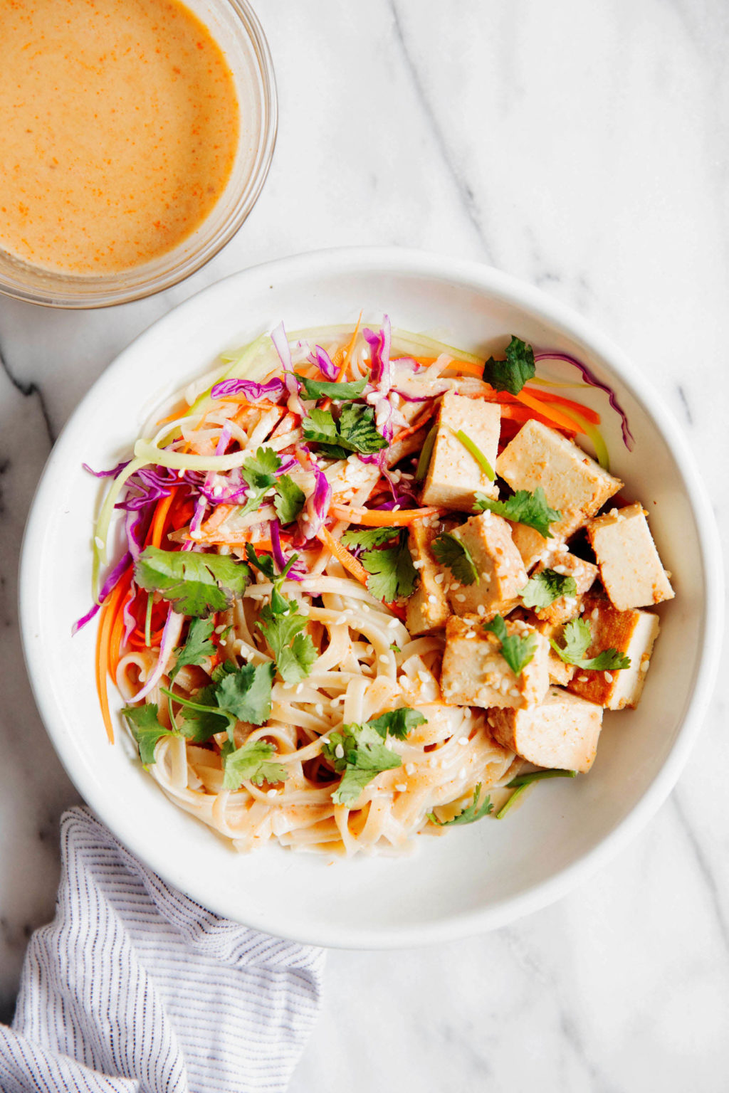 A bright teriyaki tofu noodle bowl is resting on white marble, with a small bowl of sauce nearby.