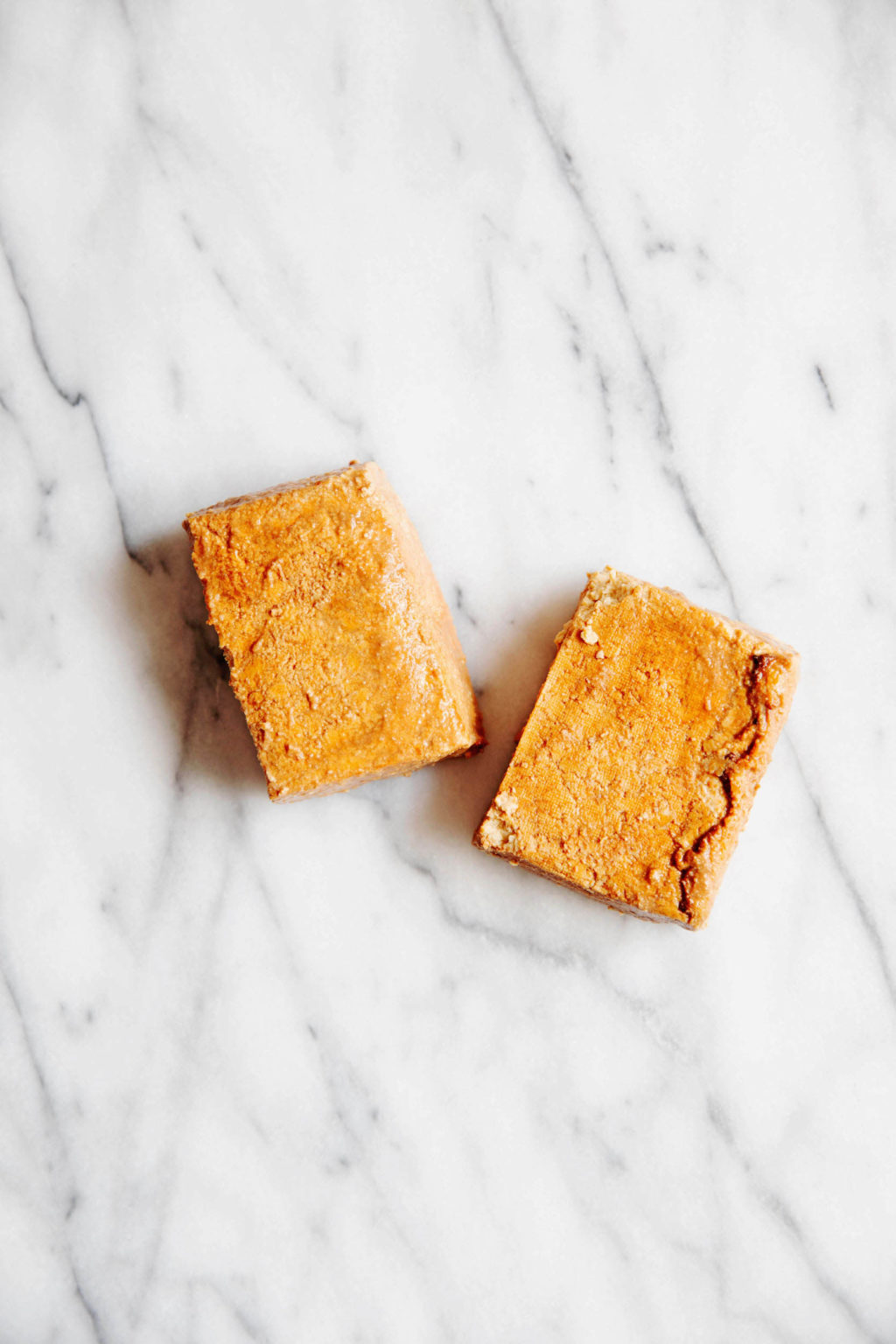 Two blocks of marinated, baked tofu rest on a marble surface.