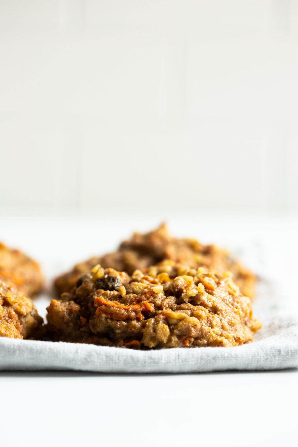 A few chewy, oatmeal breakfast cookies are placed on a pale linen napkin against a bright backdrop.