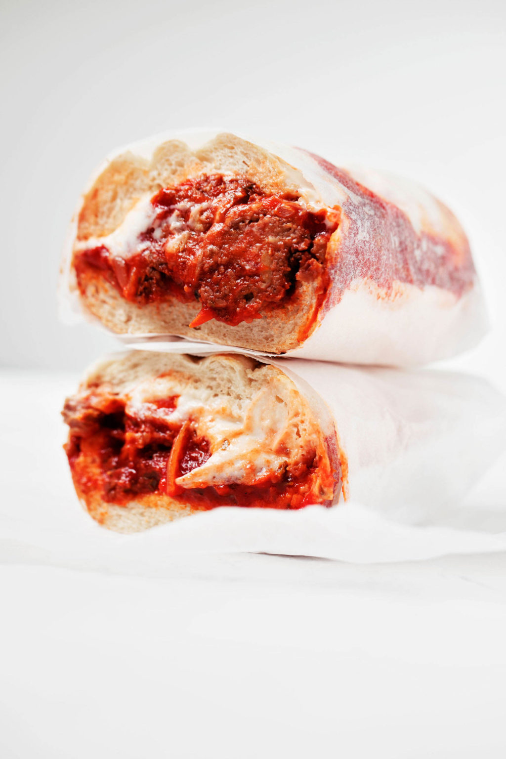 A vegan tempeh meatball sub is wrapped in parchment paper and resting on a white surface.