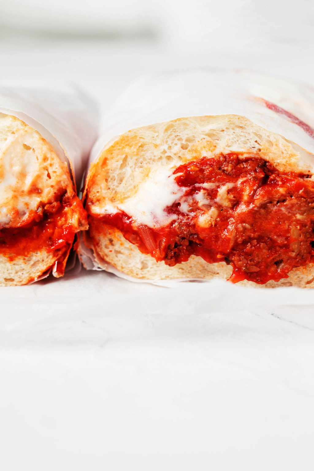 A vegan Italian meatball sub, made with tempeh, has been sliced in half crosswise. A cross section of the sandwich is shown against a white background.