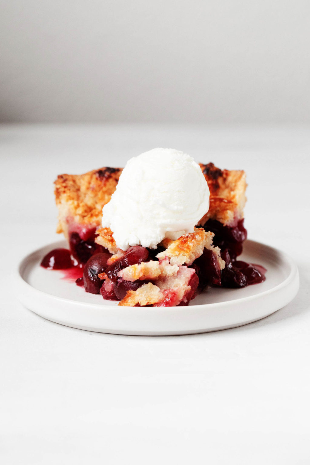 A slice of rustic, fruit dessert rests on a small, round white dessert plate. The flaky dessert is topped with a white scoop of vanilla ice cream.