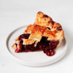 A slice of cherry pie rests on a small, white dessert plate. It's filled with juicy cherries and has a lattice top crust.