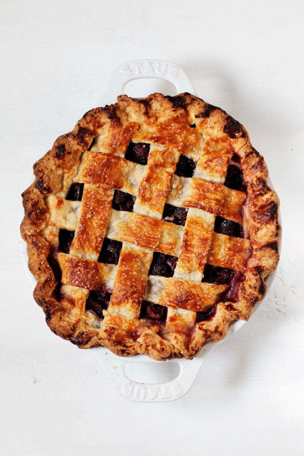A dark golden, freshly baked fruit dessert with a lattice top crust is resting in a white round baking dish.