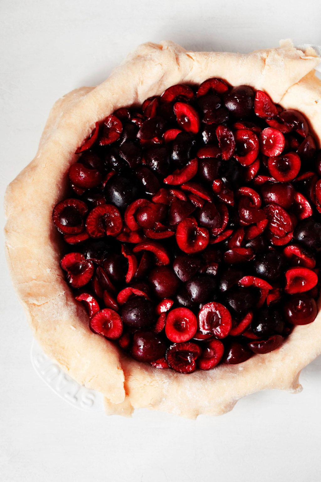 Dark, sweet cherries have been piled into a crust-lined pie baking dish.