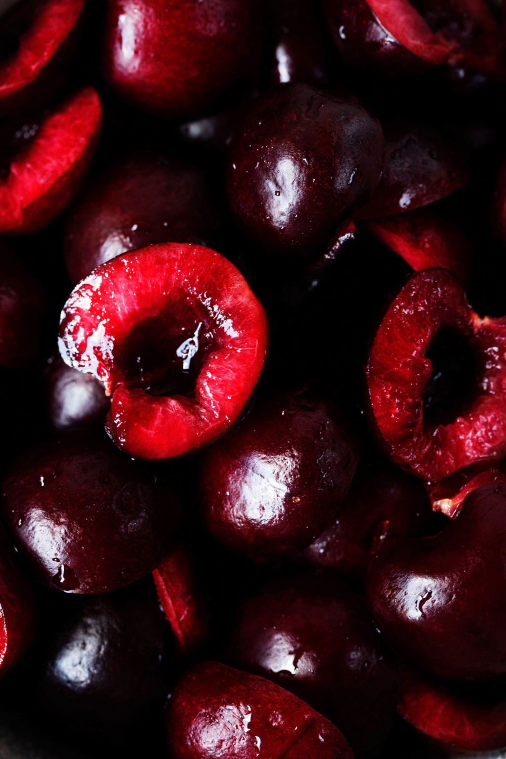A zoomed in photograph of cut, dark red stone fruits.