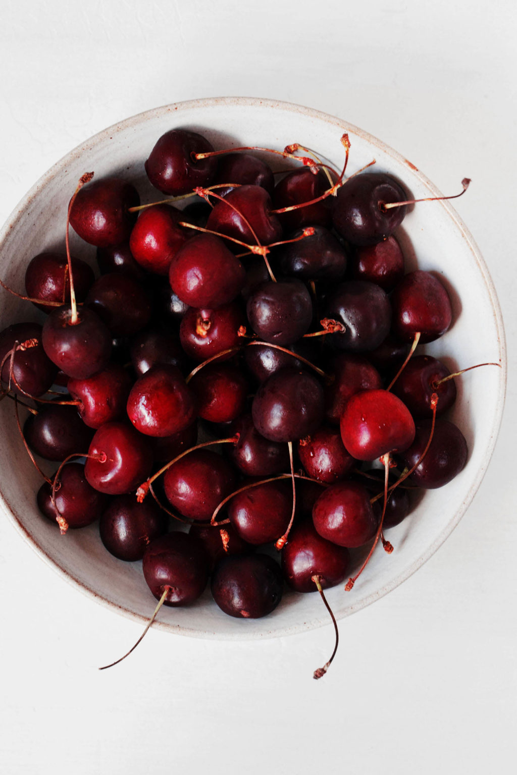 A bowl of whole, dark red sweet cherries. The white bowl is pictured against a white backdrop.