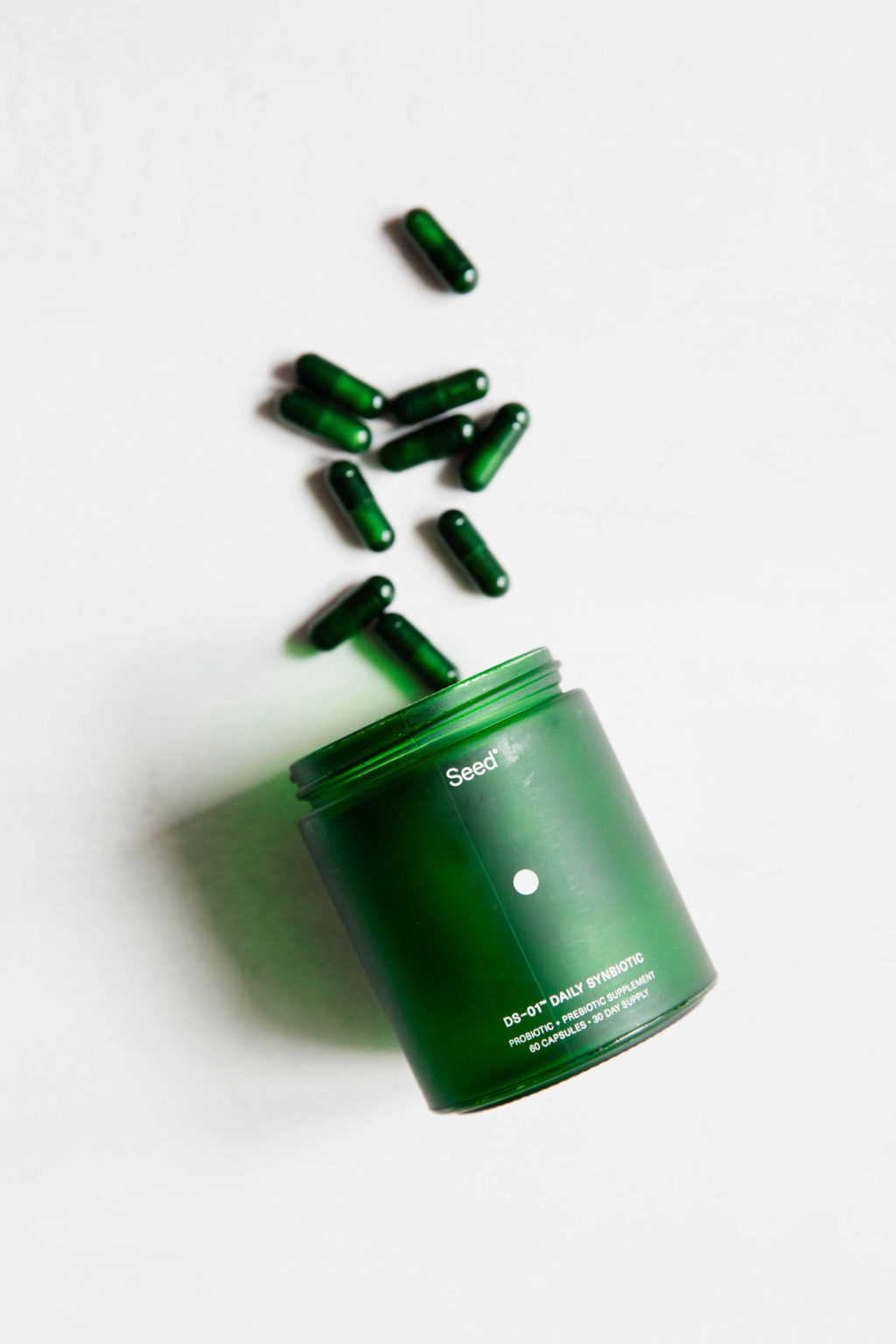 A green bottle is laid on a white surface, with green capsule shaped pills tumbling out beside it.