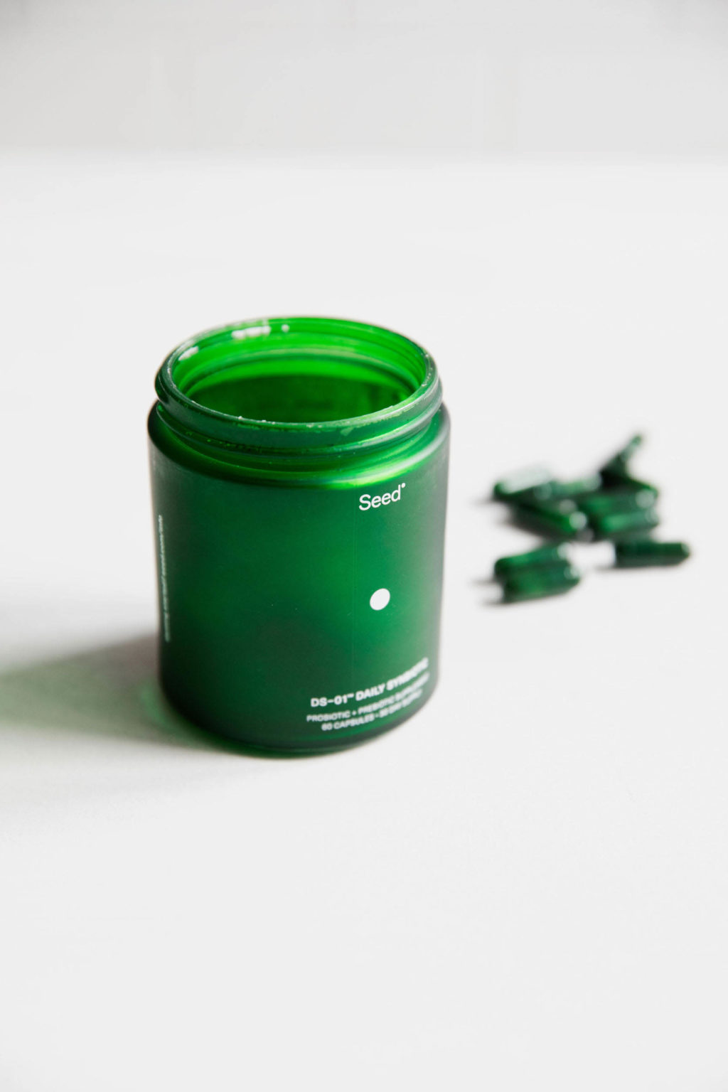 A green, glass pill bottle is standing atop a white surface.