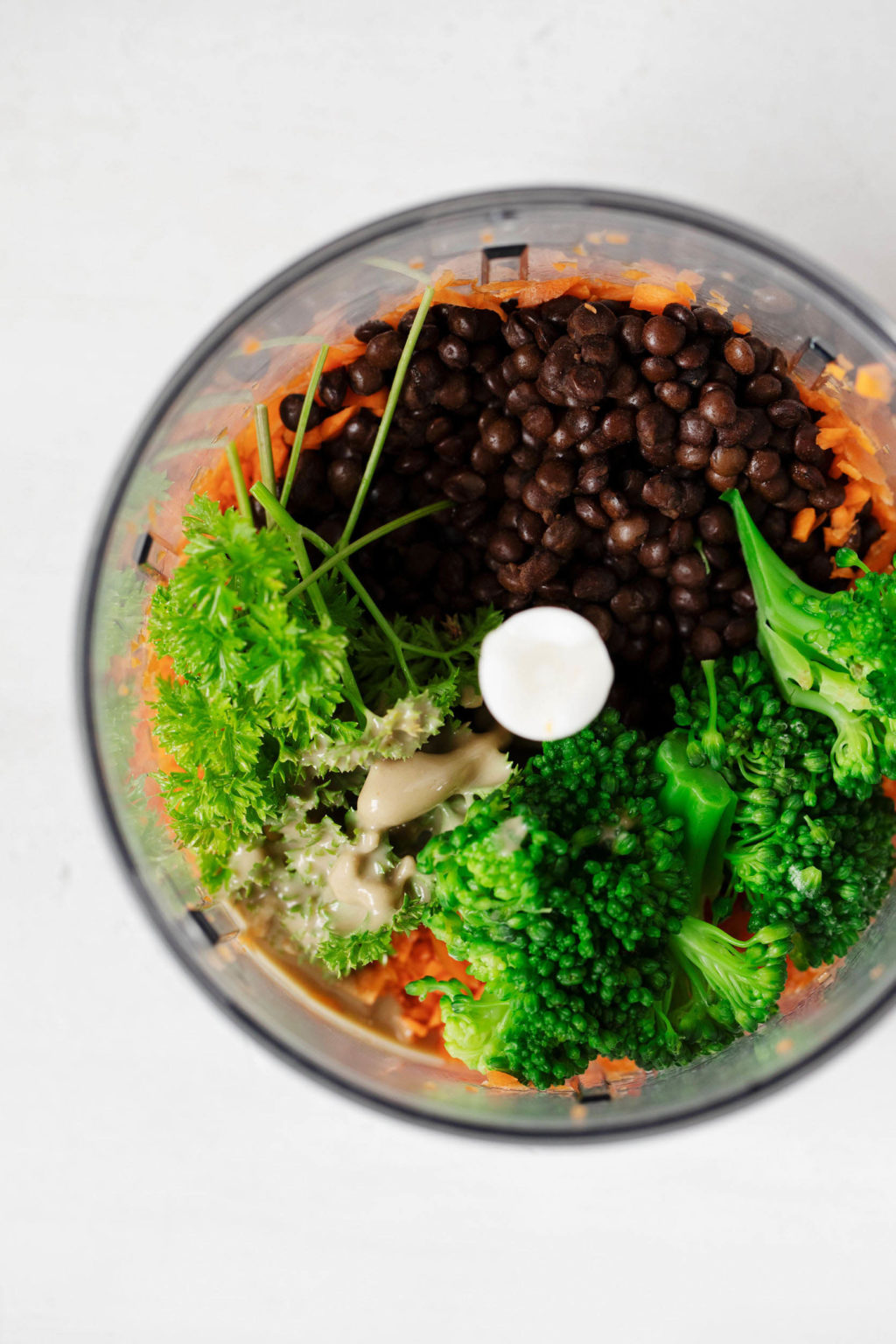 The bowl of a food processor is filled with lentils, broccoli, carrots, and herbs.