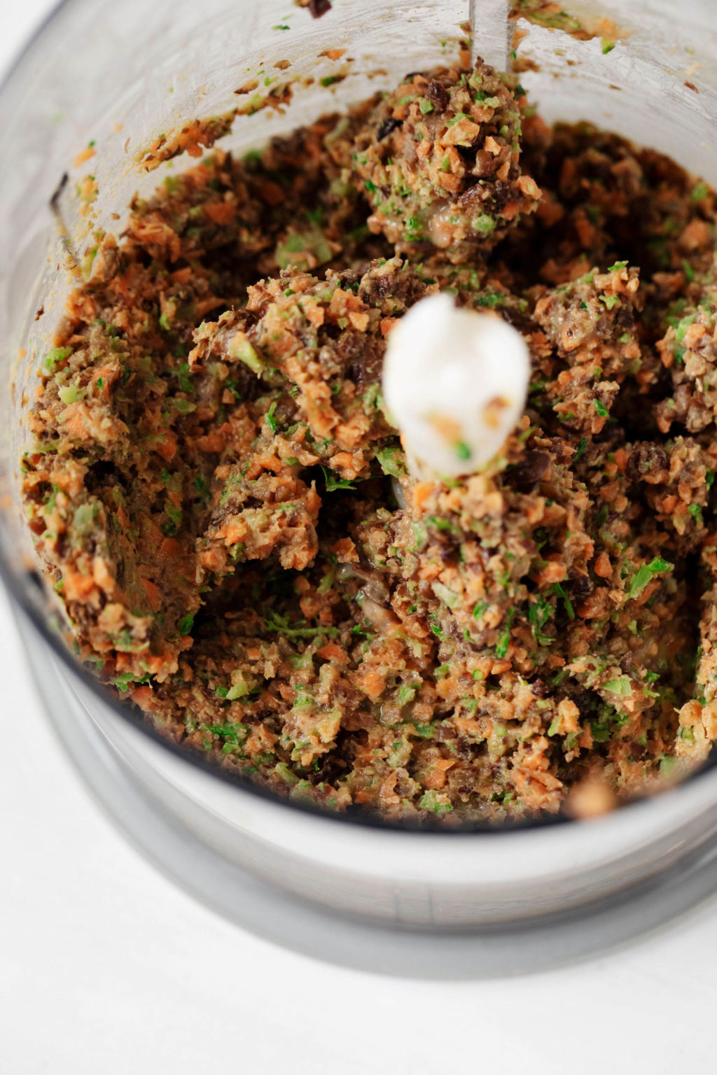 The bowl of a food processor is filled with finely chopped vegetables, lentils, herbs, and lemon juice.