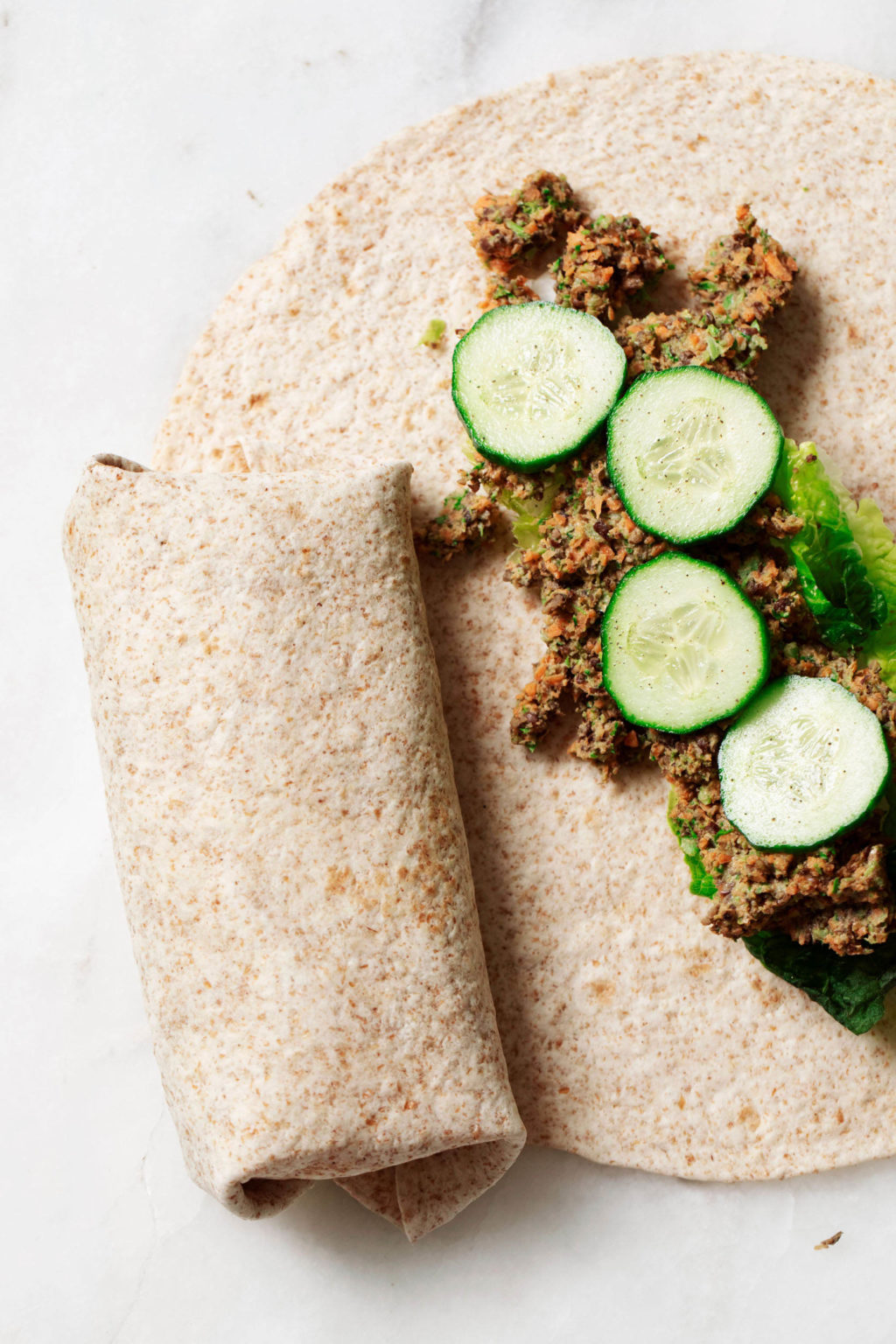 Lentil tahini wraps are being prepared on a white work surface. They're stuffed with cucumber slices and a lentil vegetable filling.