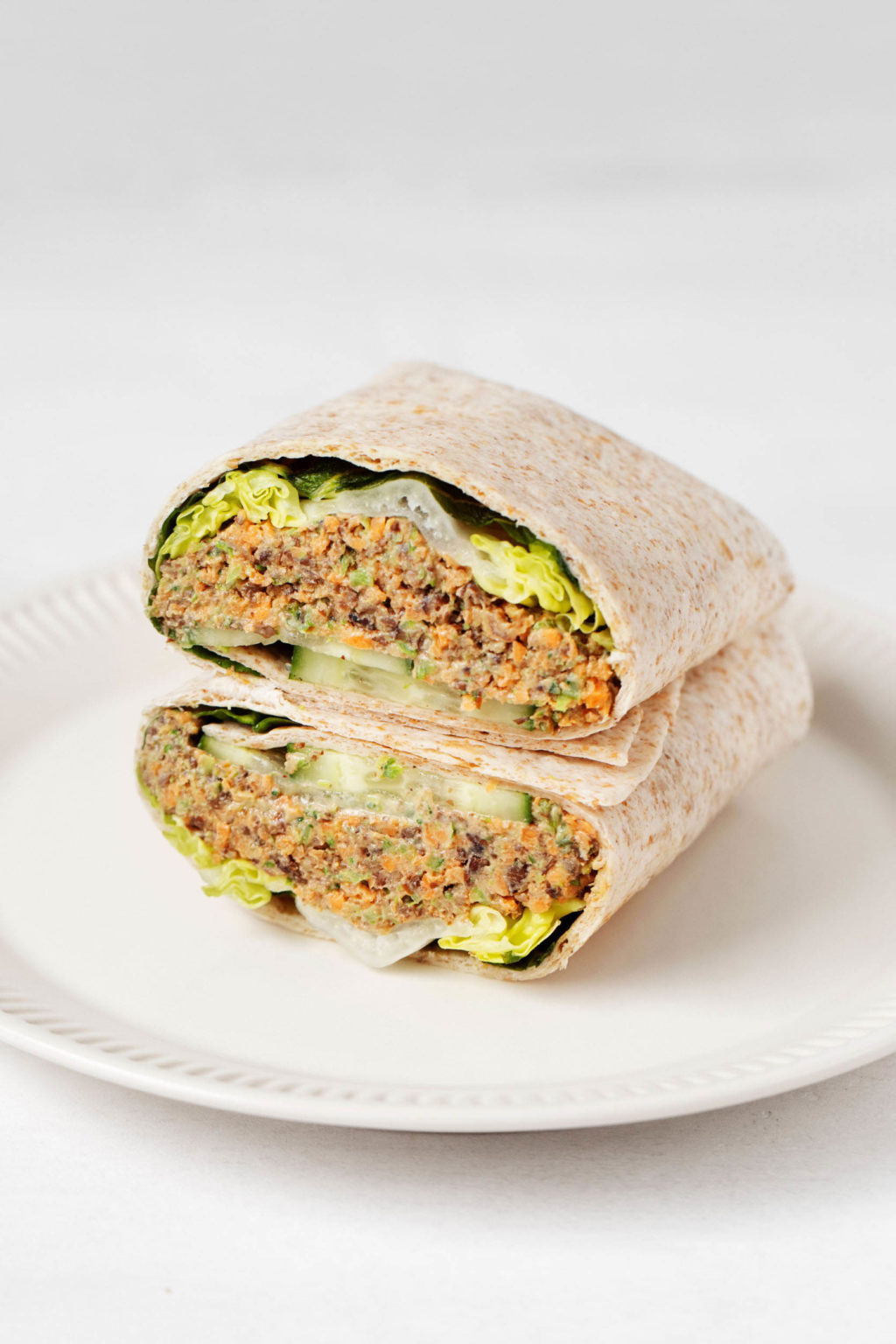 A cream colored, rimmed serving plate holds a whole grain wrap that has been sliced in half crosswise. It's filled with vegetables and legumes.