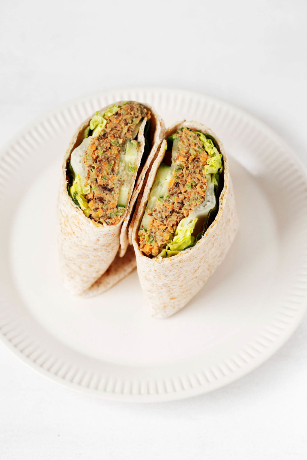 A vegan lentil tahini wrap has been sliced in half. It's placed, cut side up, on a cream colored serving dish.