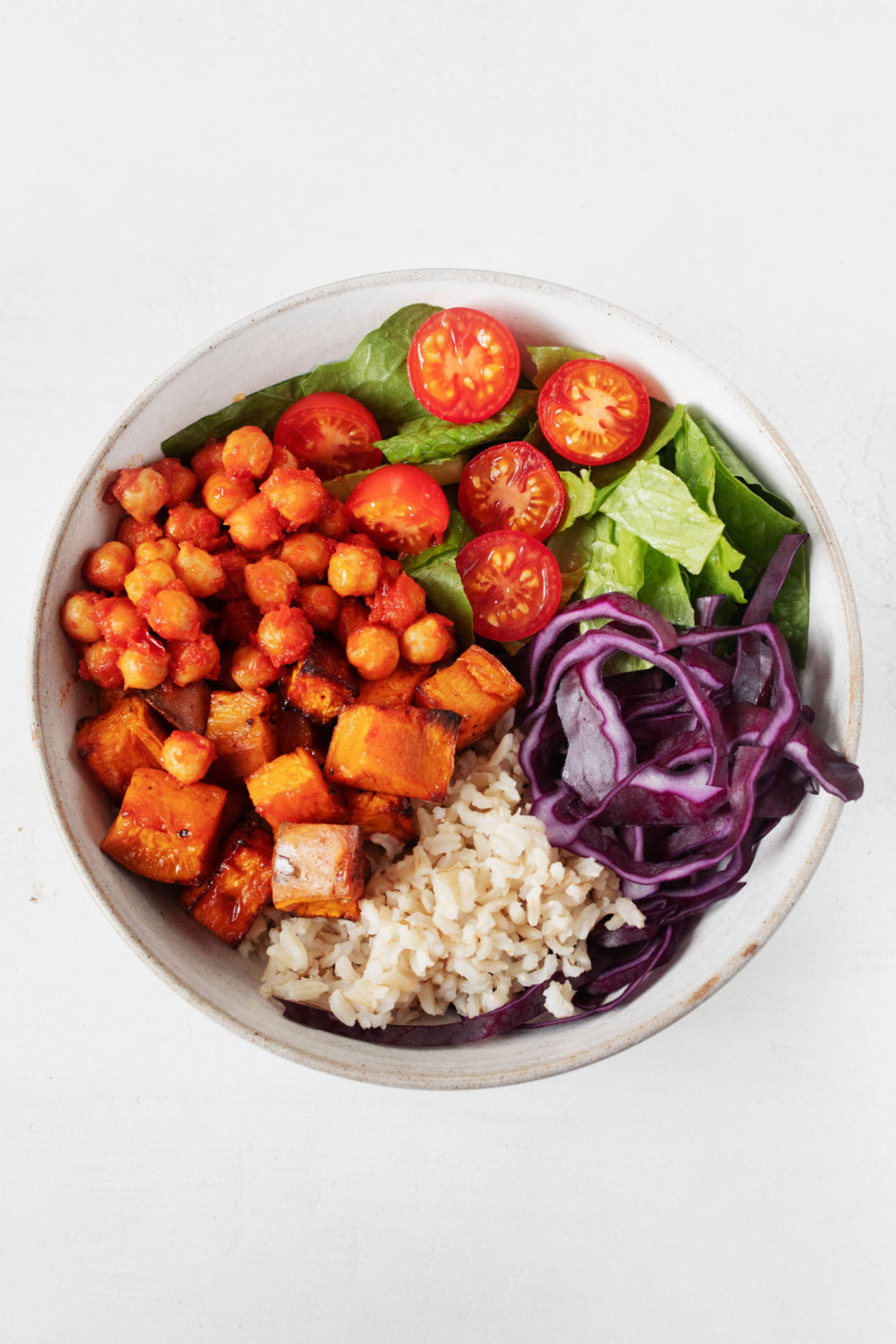 An overhead image of a white bowl containing seasoned chickpeas, rice, and vegetables.
