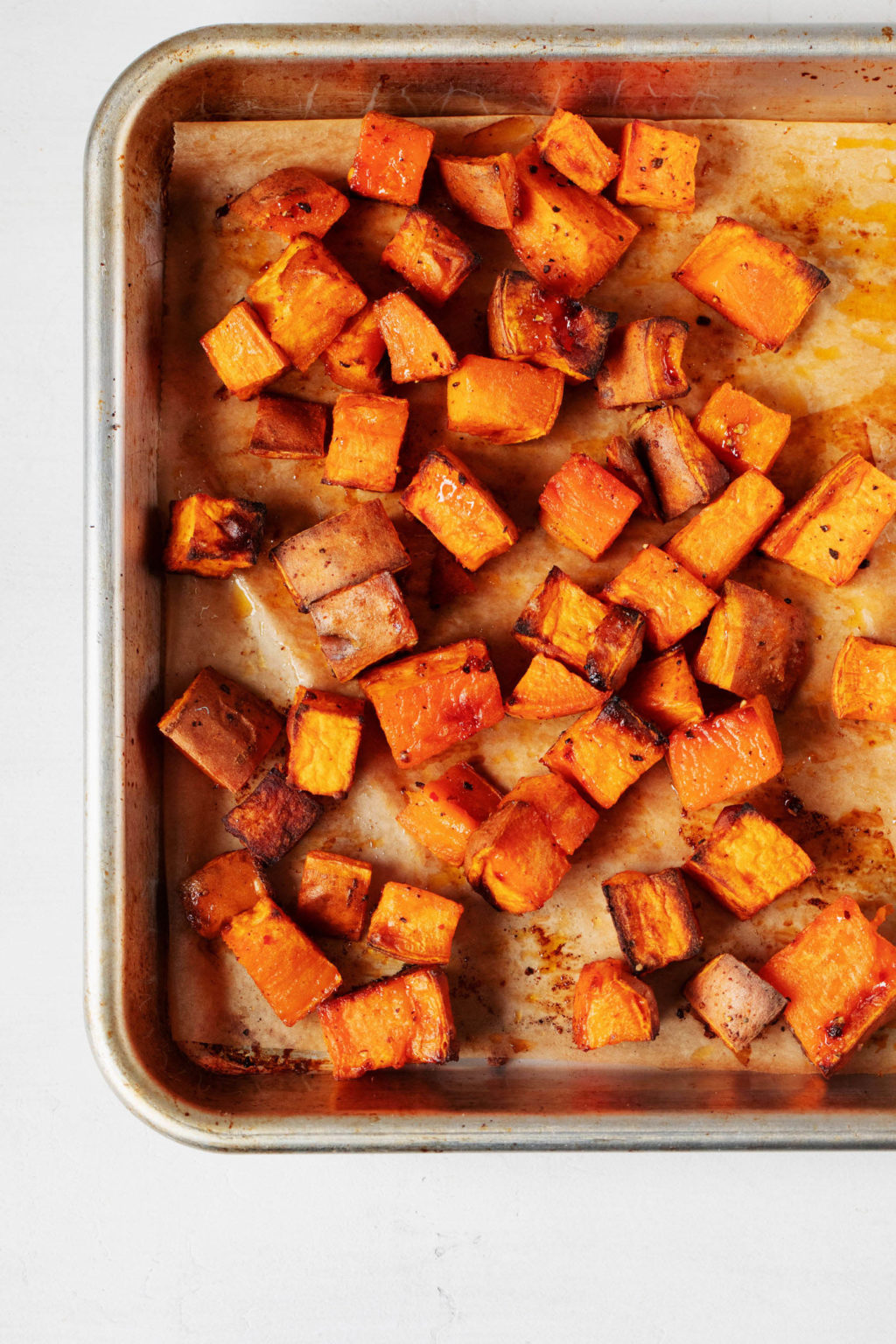 A lined sheet pan has been covered with cubes of roasted sweet potato.
